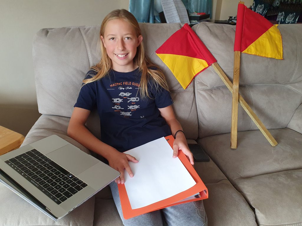 A volunteer with some paperwork, a computer and semaphore flags