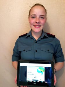 AC Rebecca standing in uniform showing an image of a certificate on a computer screen