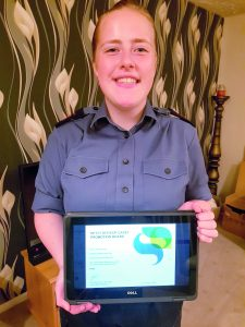 LC Emma standing in uniform showing an image of a certificate on a computer screen